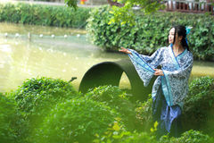 Asian Chinese woman in traditional Blue and white Hanfu dress, play in a famous garden ,sit on an ancient stone chair Stock Images
