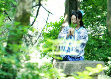 Asian Chinese woman in traditional Blue and white Hanfu dress, play in a famous garden ,sit on an ancient stone chair Royalty Free Stock Image