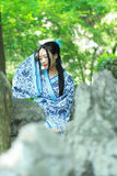 Asian Chinese woman in traditional Blue and white Hanfu dress, play in a famous garden ,sit on an ancient stone chair Royalty Free Stock Photo