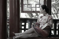 Asian Chinese woman in traditional cheongsam enjoy free time Royalty Free Stock Image