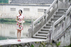 Asian Chinese woman in traditional cheongsam stand on a ancient bridge Stock Images