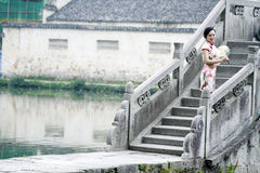 Asian Chinese woman in traditional cheongsam stand on a ancient bridge Royalty Free Stock Images