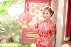 The Asian Chinese woman in Traditional Chinese hold red paper stock photo