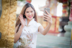 Asian Chinese woman in Traditional Chinese and hold telephone. By background ambience China royalty free stock photography