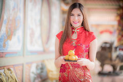 The Asian Chinese woman in Traditional Chinese holding orange pa. Asian Chinese woman in Traditional Chinese holding orange pay respect royalty free stock photos
