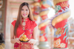 The Asian Chinese woman in Traditional Chinese holding orange pa. Asian Chinese woman in Traditional Chinese holding orange pay respect stock photo