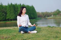 Peaceful quite happy life, Asian Chinese yoga woman girl beauty by lake river sea ocean. Asian Chinese woman yoga by a lake, capped mountains on the background royalty free stock photos