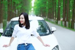 Free carelss happy woman enjoy cozy comfortable life drive a white car on a road in forest. Asian Chinese woman yoga by a lake, capped mountains on the Stock Image