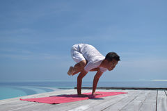 Asian chinese man in yoga pose by the sea Royalty Free Stock Photo