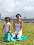 Asian chinese woman practising yoga outdoors with young baby gir. Asian chinese women practising yoga outdoors watched by a baby girl Royalty Free Stock Photos