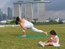 Asian chinese woman practising yoga outdoors with young baby gir Stock Image