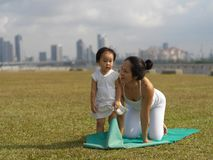 Asian chinese woman practising yoga outdoors with young baby gir Stock Photo