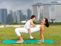 Asian chinese woman practising yoga outdoors with young baby gir Royalty Free Stock Images