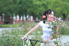 Asian Chinese Young beautiful, elegantly dressed woman with Sharing bicycle. Beauty, fashion and lifestyle stock photo