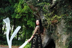 Asian Chinese Young girl dance in front of an old tree. Asian Chinese Young beautiful woman enjoy free time, beautiful graceful girl, healthy living concept Royalty Free Stock Image