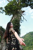 Asian Chinese Young girl dance and pray in front of an old tree. Asian Chinese Young beautiful woman enjoy free time, beautiful graceful girl, healthy living Royalty Free Stock Images