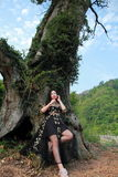 Asian Chinese Young girl dance and pray in front of an old tree. Asian Chinese Young beautiful woman enjoy free time, beautiful graceful girl, healthy living Stock Photo