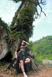 Asian Chinese Young girl dance and pray in front of an old tree. Asian Chinese Young beautiful woman enjoy free time, beautiful graceful girl, healthy living Royalty Free Stock Photography