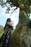 Asian Chinese Young girl dance and pray in front of an old tree. Asian Chinese Young beautiful woman enjoy free time, beautiful graceful girl, healthy living Stock Image