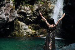 Asian Chinese Young girl dance before waterfall. Asian Chinese Young beautiful woman enjoy free time, beautiful graceful girl, healthy living concept, pure Stock Images