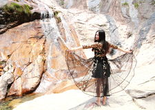 Asian Chinese Young girl dance before waterfall. Asian Chinese Young beautiful woman enjoy free time, beautiful graceful girl, healthy living concept, pure Royalty Free Stock Image
