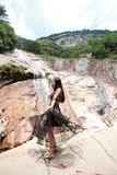 Asian Chinese Young girl dance before waterfall. Asian Chinese Young beautiful woman enjoy free time, beautiful graceful girl, healthy living concept, pure Royalty Free Stock Photo