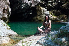 Asian Chinese Young girl do yoga before waterfall. Asian Chinese Young beautiful woman enjoy free time, beautiful graceful girl, healthy living concept, pure Stock Photography