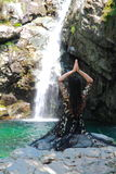 Asian Chinese Young girl do yoga before waterfall. Asian Chinese Young beautiful woman enjoy free time, beautiful graceful girl, healthy living concept, pure Royalty Free Stock Images