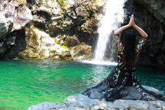 Asian Chinese Young girl do yoga before waterfall. Asian Chinese Young beautiful woman enjoy free time, beautiful graceful girl, healthy living concept, pure Stock Image