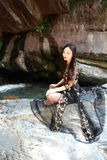 Asian Chinese Young girl do yoga before waterfall. Asian Chinese Young beautiful woman enjoy free time, beautiful graceful girl, healthy living concept, pure Royalty Free Stock Photography