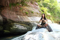 Asian Chinese Young girl do yoga before waterfall. Asian Chinese Young beautiful woman enjoy free time, beautiful graceful girl, healthy living concept, pure Royalty Free Stock Photo