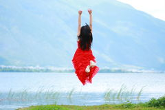 Asian Chinese Young girl jump, enjoy brilliant life by Yunnan erhai. Asian Chinese Young beautiful woman enjoy free time, beautiful graceful girl, healthy living Stock Image