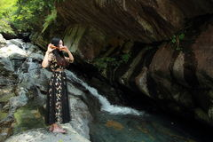 Asian Chinese Young girl play the flute before waterfall. Asian Chinese Young beautiful woman enjoy free time, beautiful graceful girl, healthy living concept Royalty Free Stock Photos