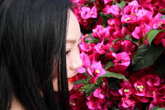 Asian Chinese Young girl smell faint aroma of flowers. Asian Chinese Young beautiful woman enjoy free time, beautiful graceful girl, healthy living concept, pure Royalty Free Stock Photography