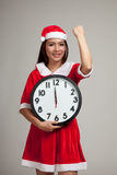 Asian Christmas girl in Santa Claus clothes and clock at midnigh Royalty Free Stock Photo
