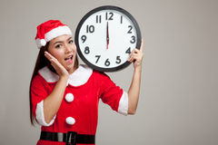 Asian Christmas girl in Santa Claus clothes and clock at midnigh Royalty Free Stock Image