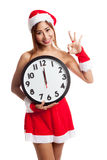 Asian Christmas girl in Santa Claus clothes and clock at midnigh Stock Image
