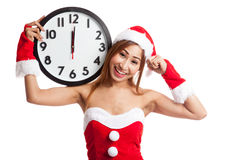 Asian Christmas girl in Santa Claus clothes and clock at midnigh Stock Photography