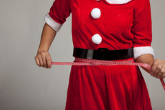Asian Christmas girl in Santa Claus clothes diet with  measuring. Tape on gray background Royalty Free Stock Photography