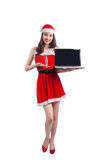 Asian Christmas girl with Santa Claus clothes holding laptop iso Stock Images