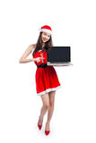 Asian Christmas girl with Santa Claus clothes holding laptop iso Royalty Free Stock Images