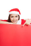 Asian Christmas girl with Santa Claus clothes point down to blan Stock Photography