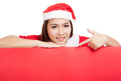 Asian Christmas girl with Santa Claus clothes point down to blan Stock Photos