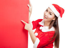 Asian Christmas girl with Santa Claus clothes point to  blank si Stock Images