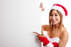 Asian Christmas girl with Santa Claus clothes point to  blank si Stock Photos