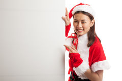 Asian Christmas girl with Santa Claus clothes point to  blank si Royalty Free Stock Photography