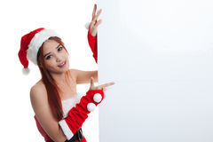 Asian Christmas girl with Santa Claus clothes point to  blank si Royalty Free Stock Images