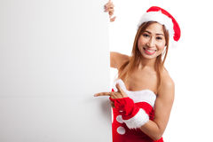 Asian Christmas girl with Santa Claus clothes point to blank sig Stock Image