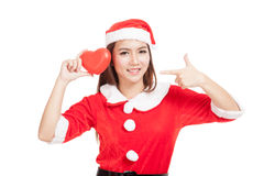 Asian Christmas girl with Santa Claus clothes point to red heart Stock Photos