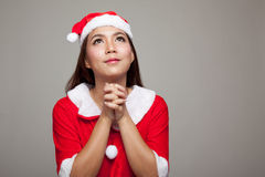 Asian Christmas girl with Santa Claus clothes is praying Royalty Free Stock Photography